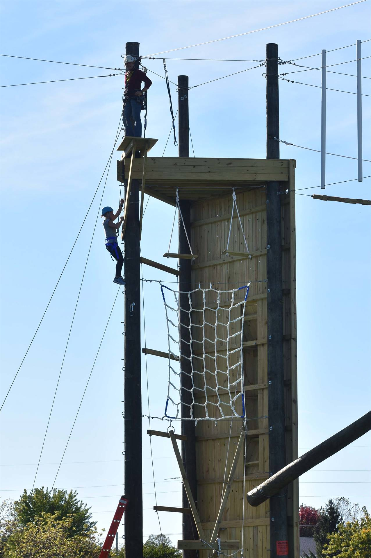 Climbing tower with ropes and two teachers