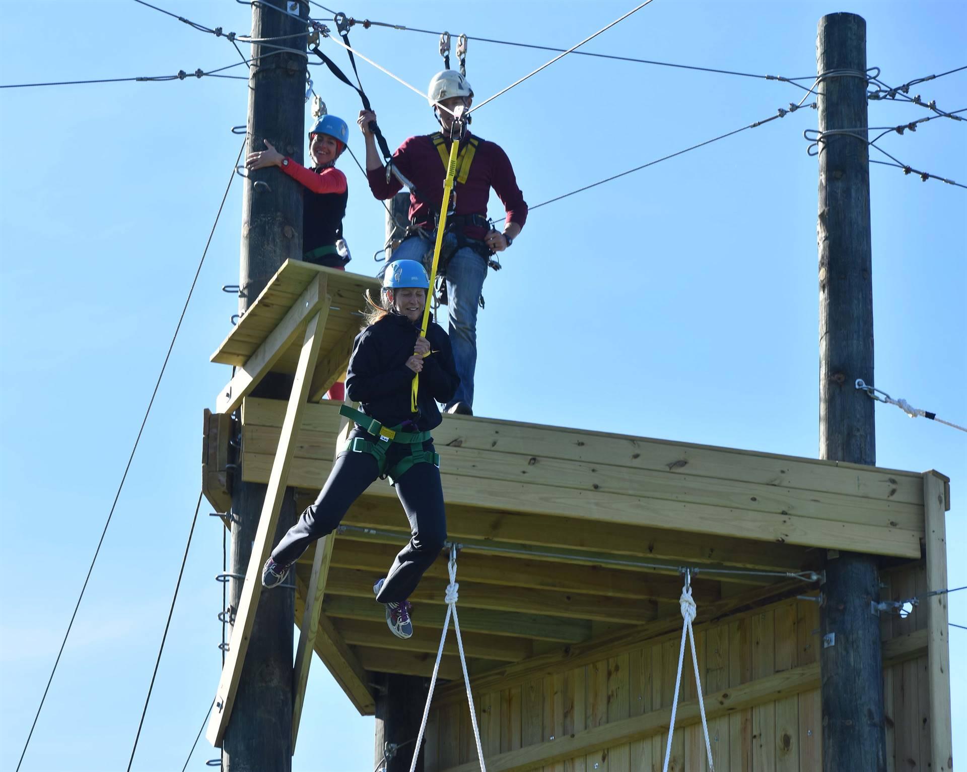 Climbing tower with teacher zip lining