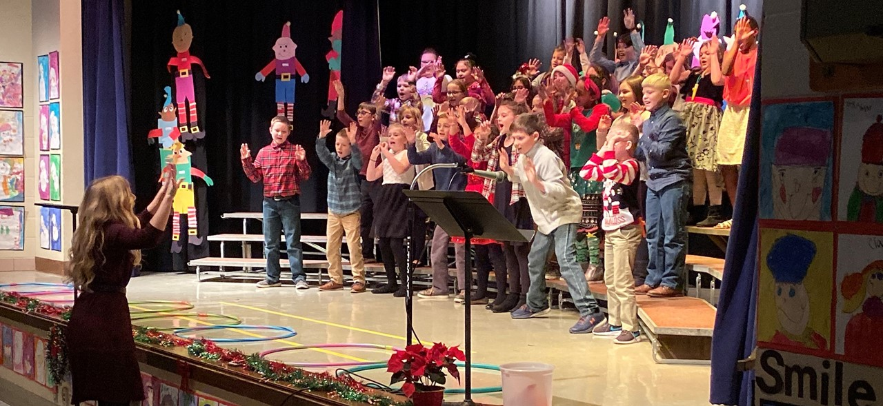 Third grade students performing on stage during their holiday concert