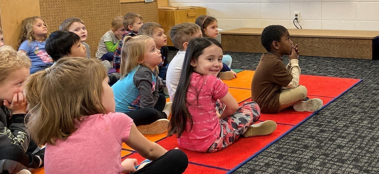 Kindergarten students listening as their teacher reads them a book at Rosenow Elementary School
