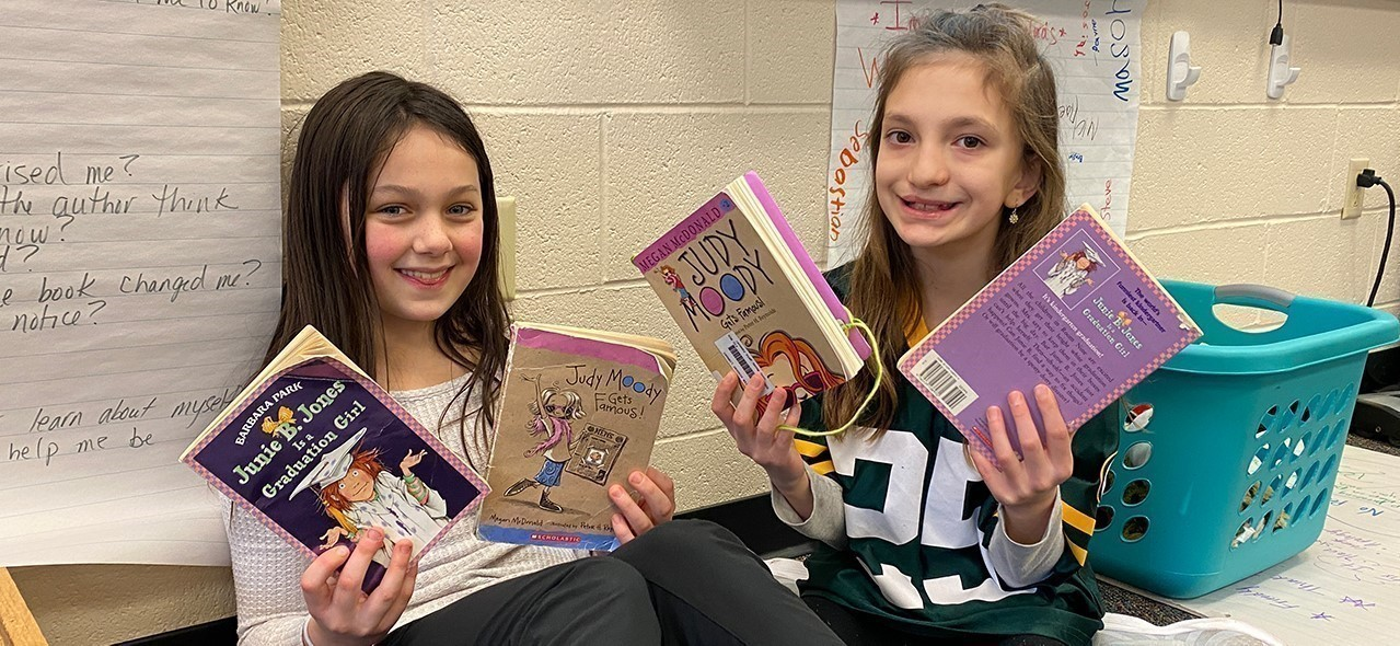 Two reading buddies with their books at STEM Academy