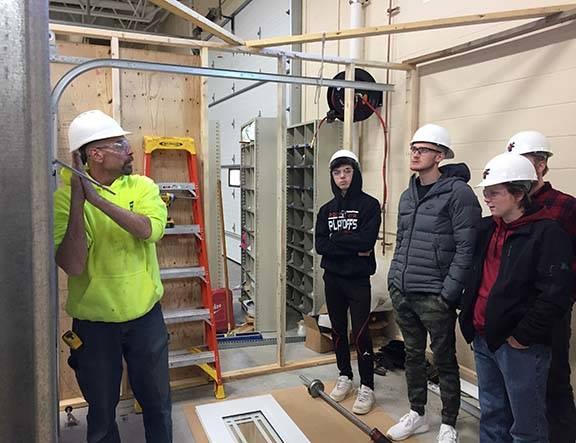 ACE students watch overhead door installation demo