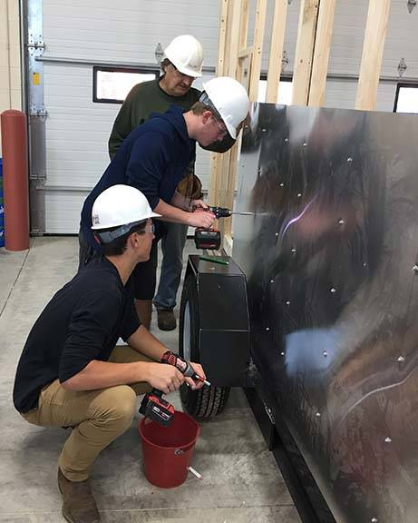ACE students drill sheet metal onto shanty frame