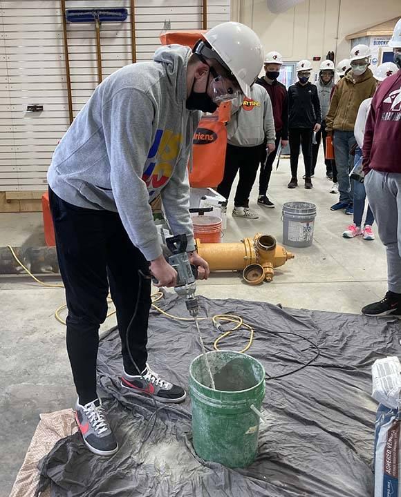 ACE student mixes mortar
