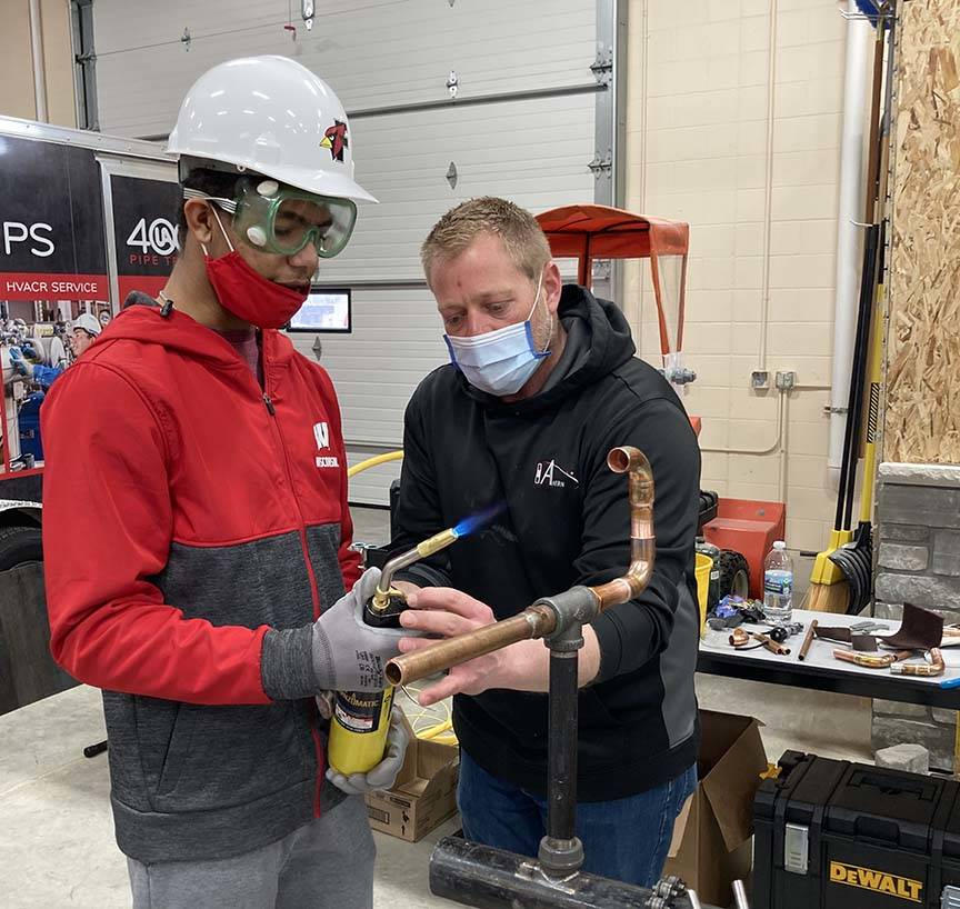 ACE student receives direction from mentor on blow torch