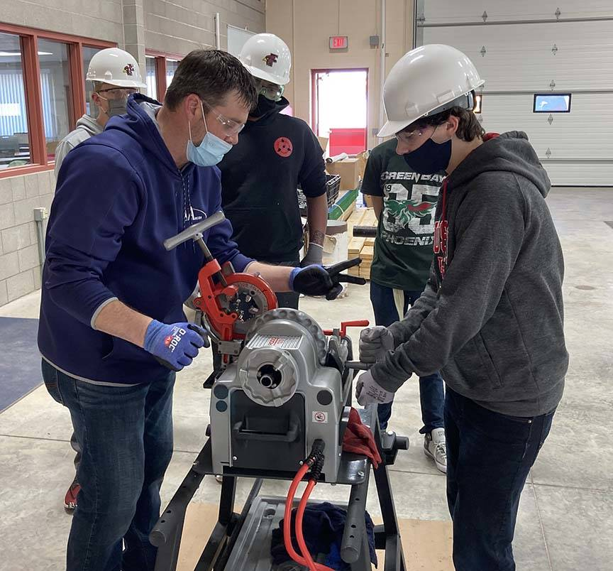 ACE student works with mentor on grinding tool