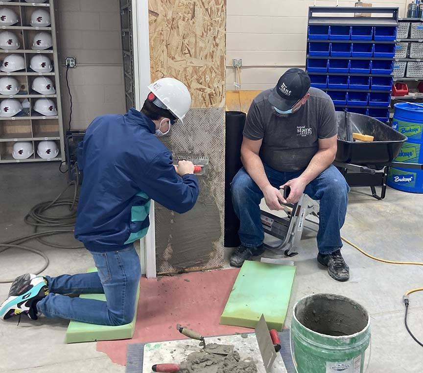 ACE student applies mortar while mason mentor provides tips
