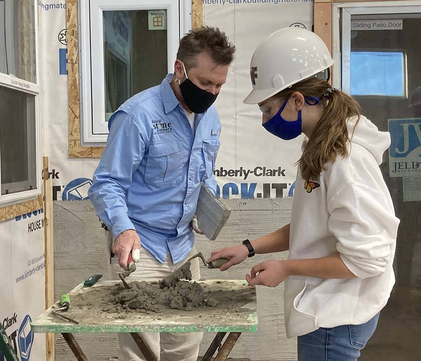 ACE student prepares mortar while mason assists