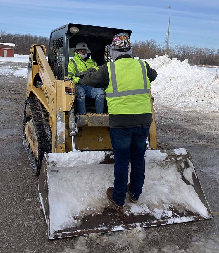 ACE student gets instruction from mentor on small cat used for snow removal