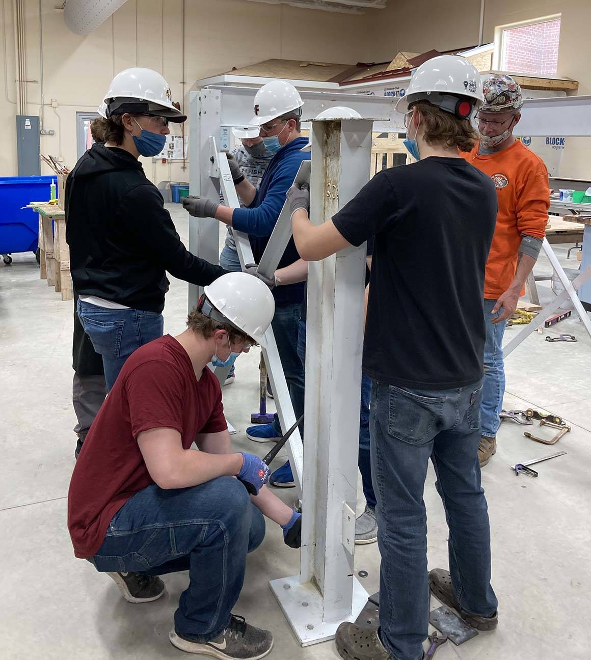 ACE students work on erecting an iron piece