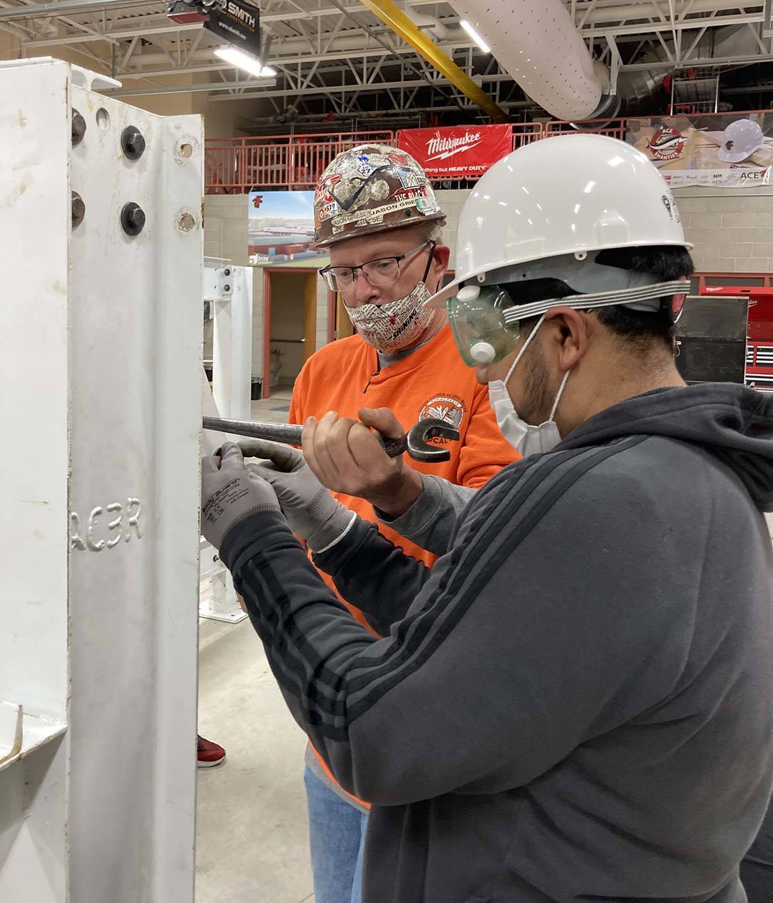 ACE student drills on iron piece while iron worker provides guidance