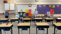 Four students demonstrating social distancing